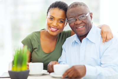 beautiful young adult african girl and father having coffee at home